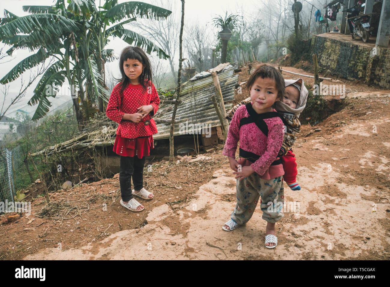 TA PHIN, LAO CAI, VIETNAM - 12 January 2019: A small child in a bag behind a child girl. Red dzao - a small nation of North Vietnam Stock Photo