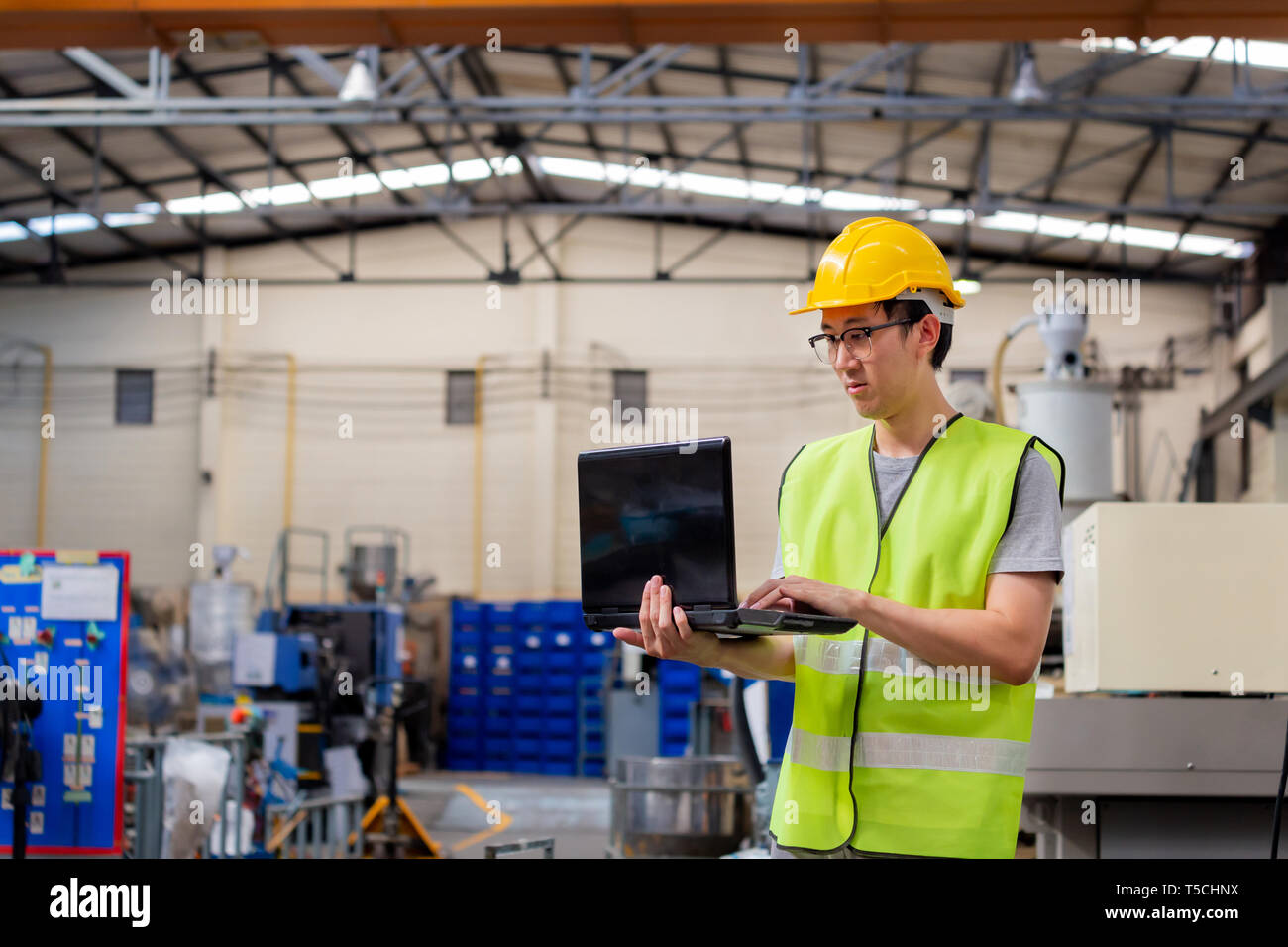 Asian male Industrial engineer in hardhat working with laptop in safety jacket at manufacturing factory. Processing plastic injection molding industry - Stock Image