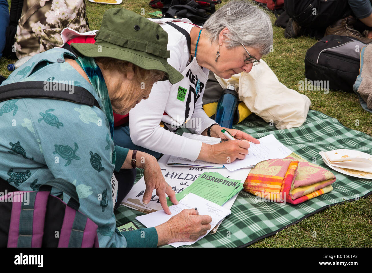 London, UK. 23rd April 2019. Climate change activists from Extinction Rebellion attending an assembly in Parliament Square write letters to their Members of Parliament requesting a meeting to discuss the issue of climate change. Activists later tried to deliver their letters to Parliament, but all but ten were prevented from doing so by the Metropolitan Police. Credit: Mark Kerrison/Alamy Live News - Stock Image