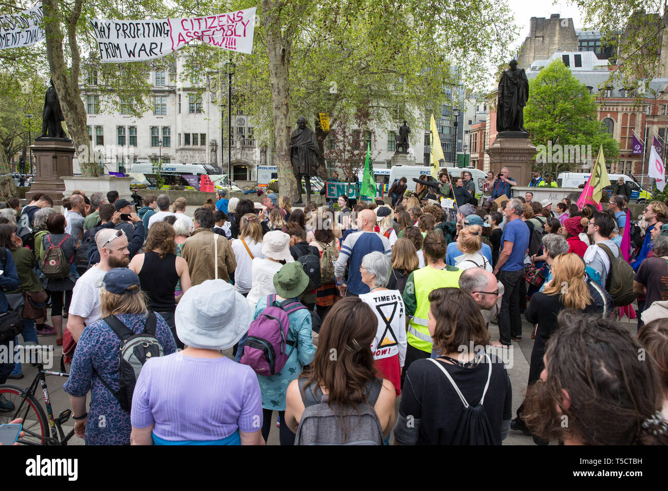 London, UK. 23rd April 2019. Climate change activists from Extinction Rebellion congregate around the statue of Gandhi during an assembly in Parliament Square before attempting to deliver letters to their Members of Parliament requesting meetings to discuss the issue of climate change. All but ten were prevented from doing so by the Metropolitan Police. Credit: Mark Kerrison/Alamy Live News - Stock Image