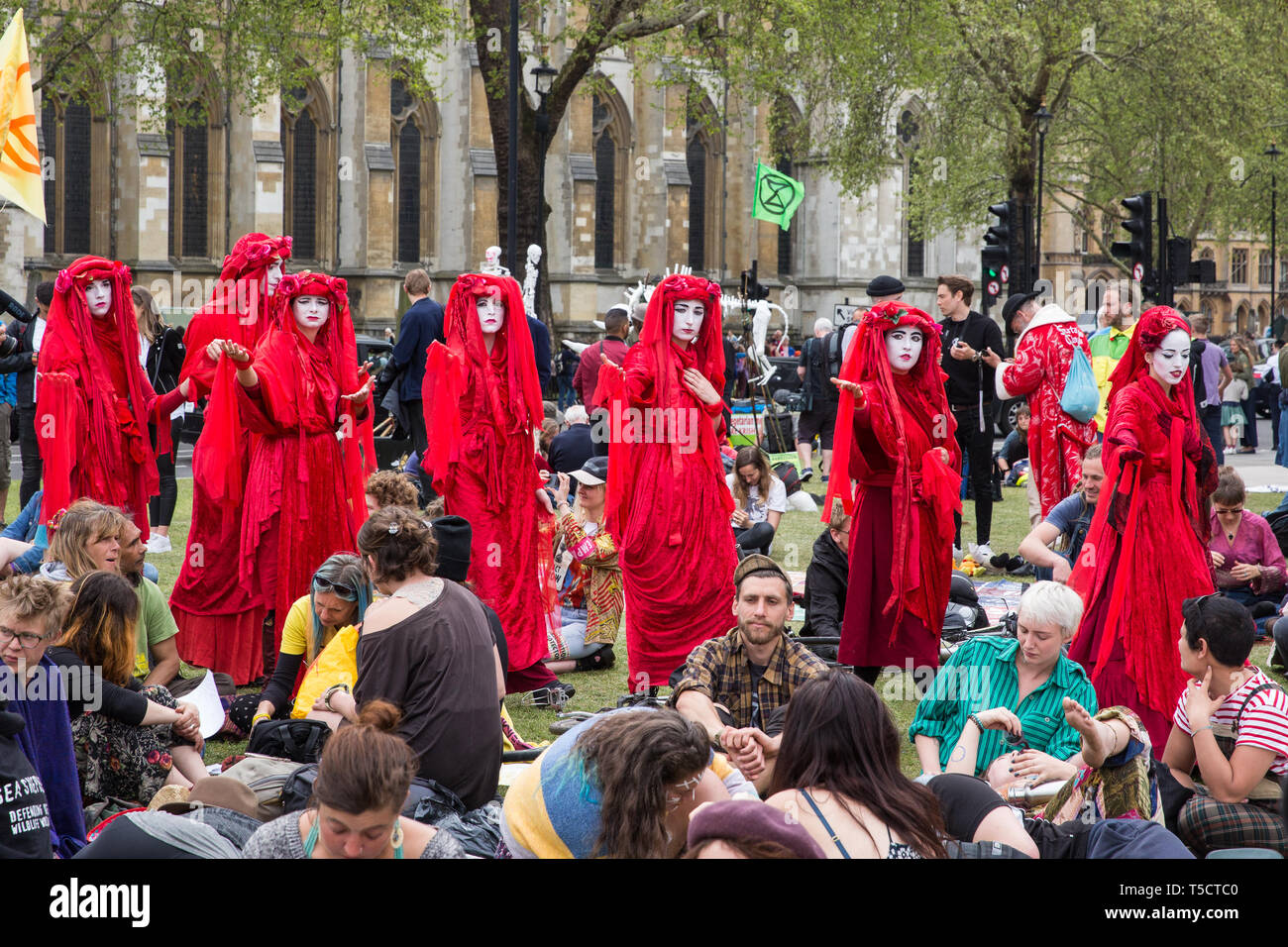 London, UK. 23rd April 2019. Climate change activists from Extinction Rebellion dressed in red to signify the blood of the dying planet cross Parliament Square during an assembly to discuss the preparation and delivery of activists' letters requesting meetings with Members of Parliament. Credit: Mark Kerrison/Alamy Live News - Stock Image