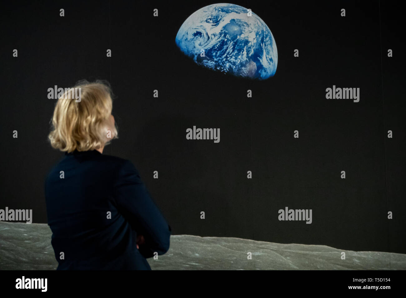 24 April 2019, Bavaria, Nürnberg: A woman observes during the exhibition 'Spaceship living room. The moon landing as a media event' the picture 'Earthrise' taken from Apollo 8. The exhibition at the Museum of Communication, which runs until 22 September 2019, documents the first globally live event - the moon landing on the night of 20 to 21 July 1969. Photo: Daniel Karmann/dpa - ATTENTION: Only for editorial use in connection with reporting about the exhibition 'Raumschiff Wohnzimmer. Die Mondlandung als Medienereignis' and only with complete mention of the above credit - Stock Image