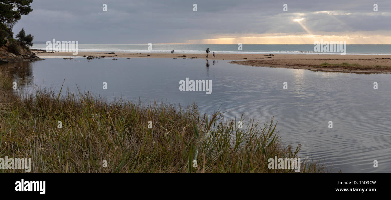Early morning sunbeams breaking through the clouds, beach and Erskine River, Lorne, Victoria, Australia - Stock Image