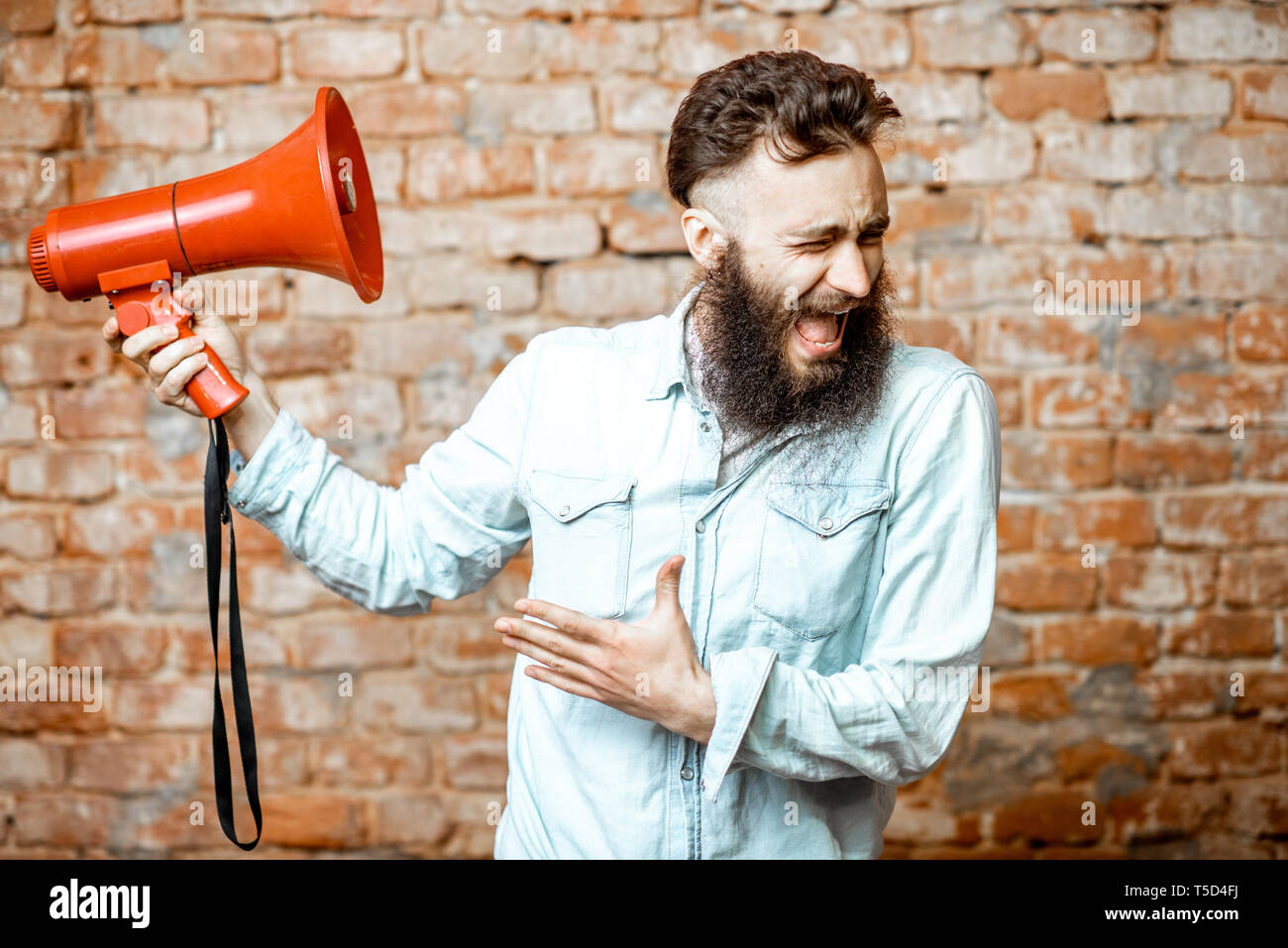 Handsome bearded man with red loudspeaker on the brick wall background - Stock Image
