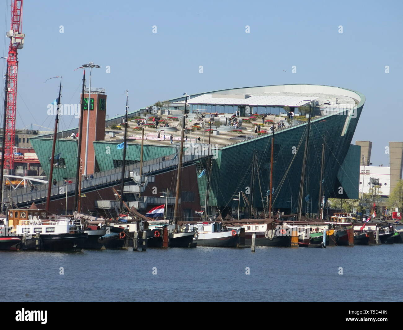 View from across the harbour of the impressive giant green hull of the boat-shaped building for NEMO Science & Technology museum in Amsterdam - Stock Image