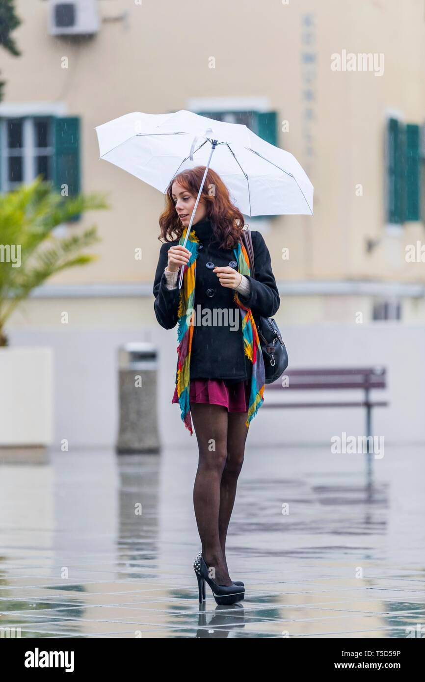 Teen girl legs heels with White umbrella in hand during dull rainy day anxious looking back over shoulder spike spiked shoes nervous Stock Photo