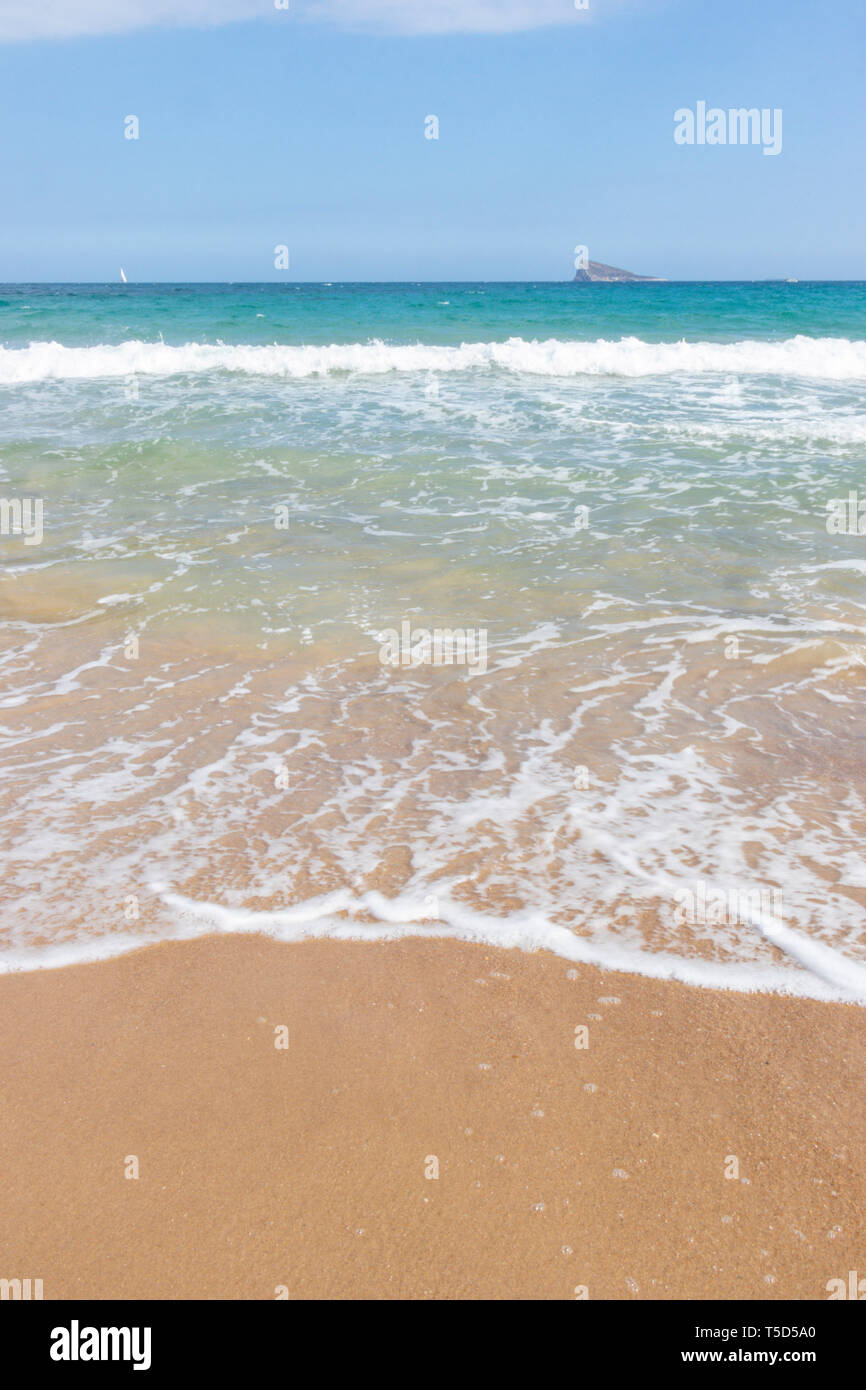 wide angle view of wave lapping beach with island in the background Alicante Spain - Stock Image