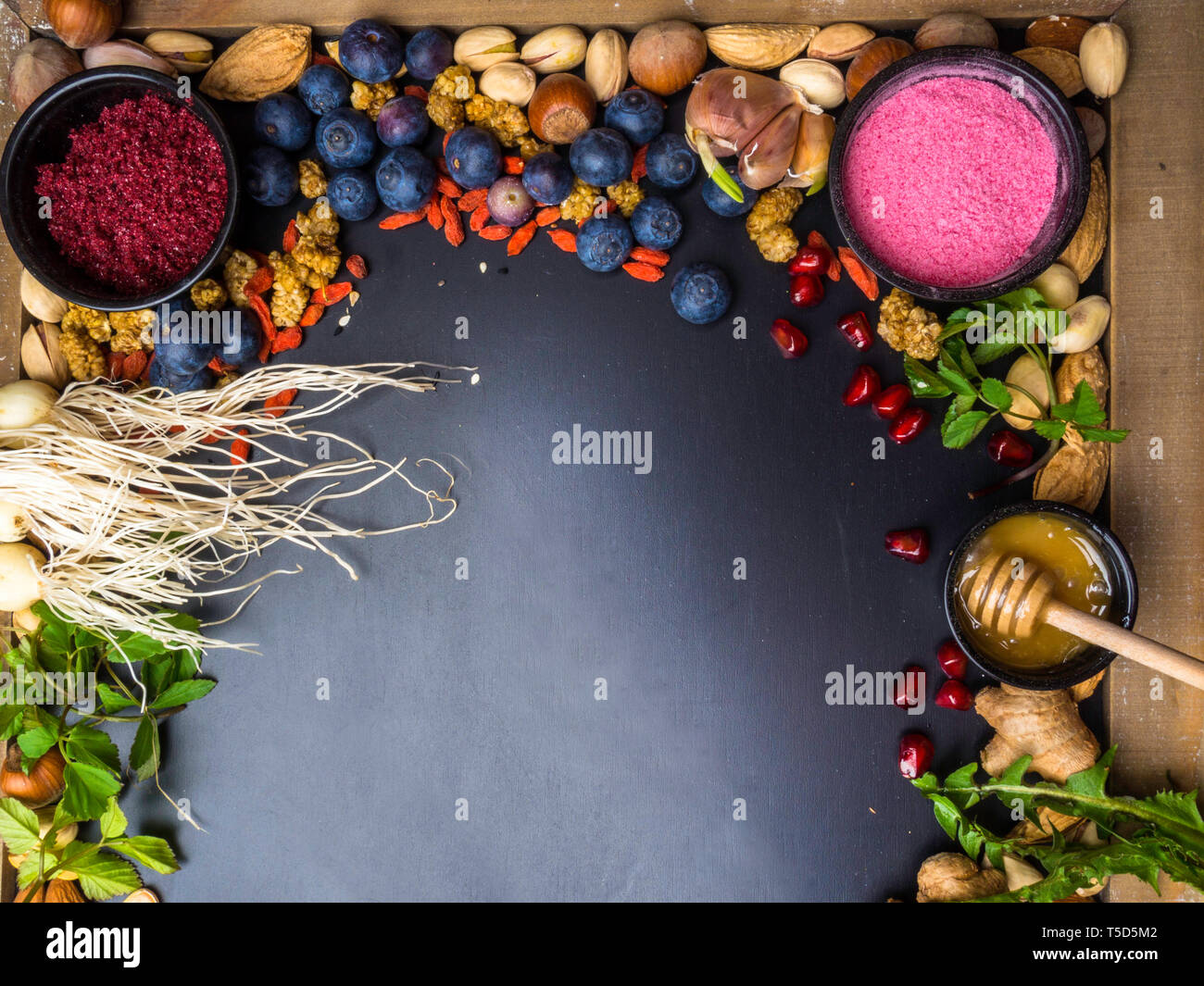 Super food or vegetarian food concept. strawberry powder,pomegranate seeds, blueberry, onion, honey, ginger, dandelion, nuts, food for healthy cooking - Stock Image