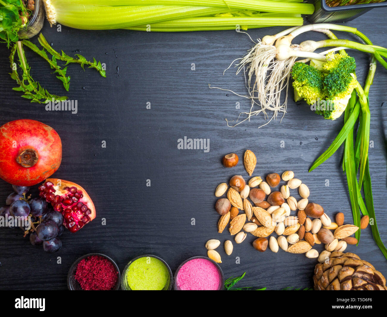 various Super foods, berry powder - strawberry, raspberry, nuts, pomegranate, grape, dandelion and selery, broccolion a wooden background, copy space - Stock Image