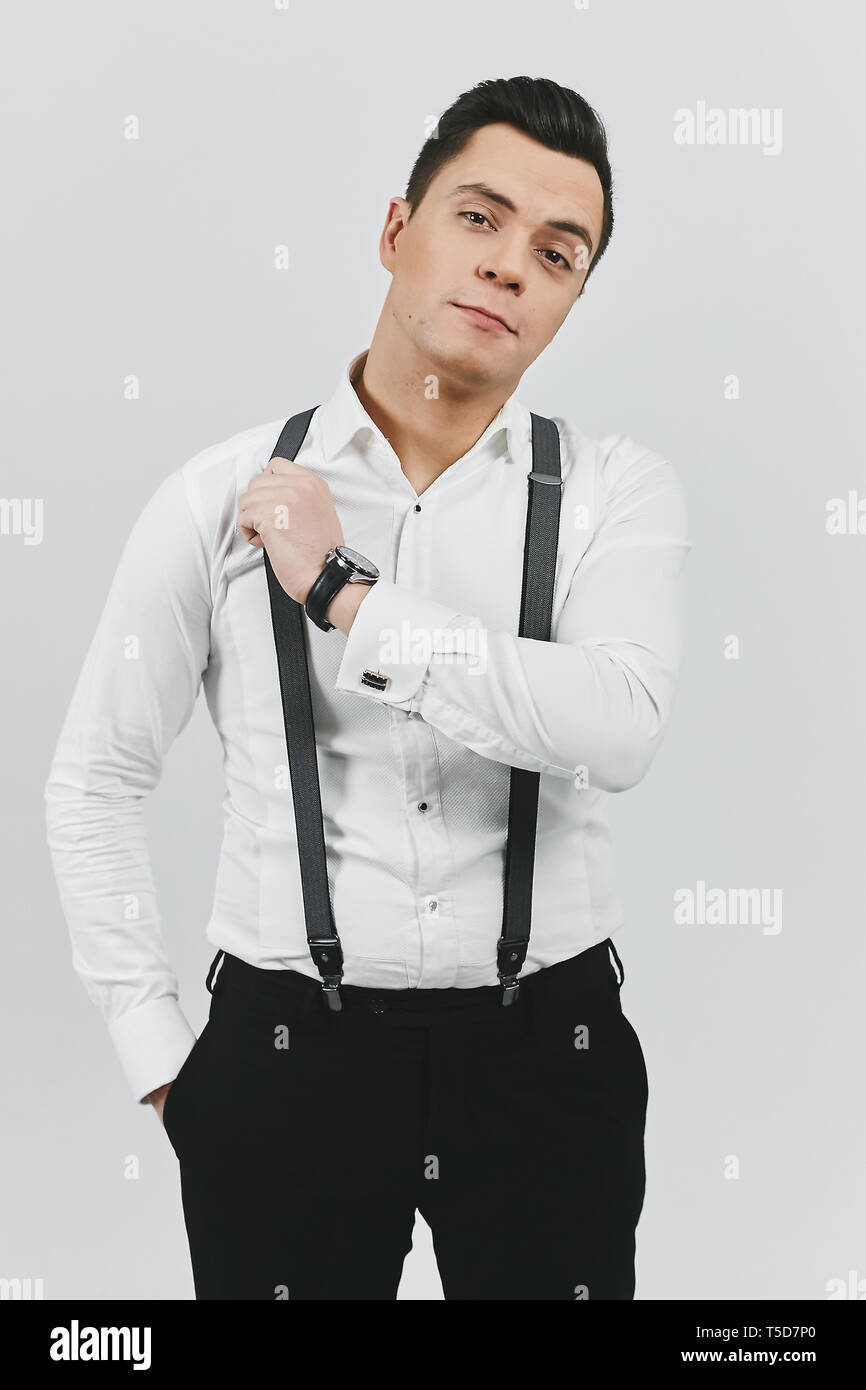 Stylish trendy young brunette man in white shirt, black pants and suspenders on white background - Stock Image