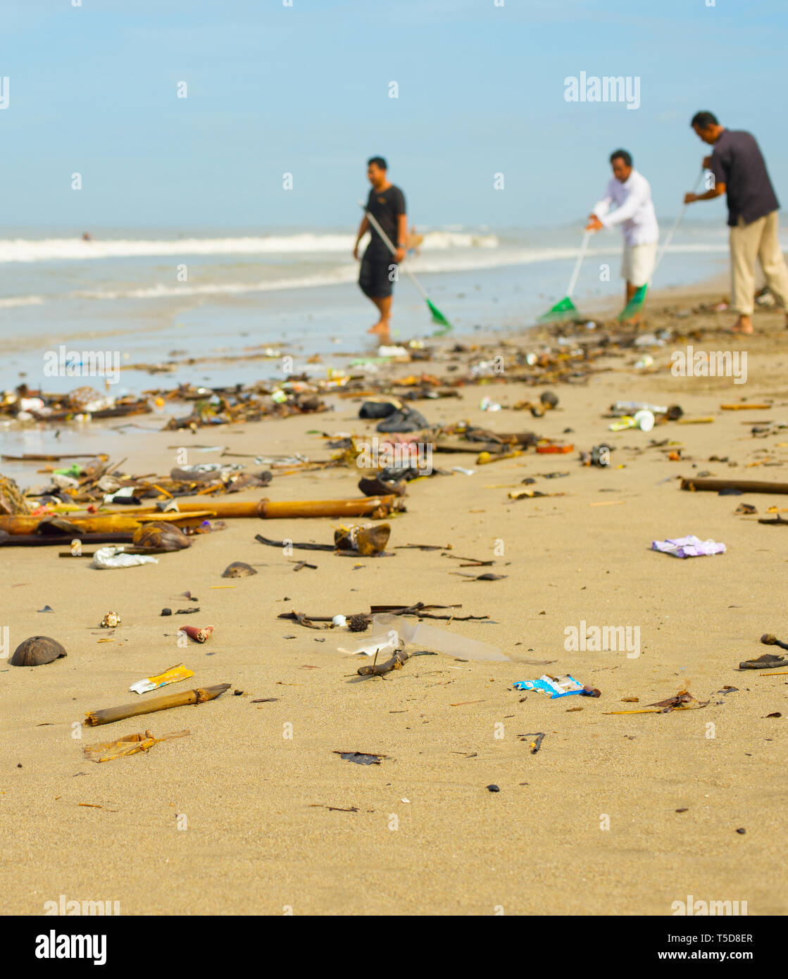 Group of people cleaning up beach from the garbage and plastic waste. - Stock Image