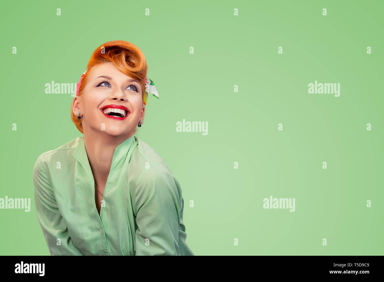 Closeup red head young excited woman pretty pinup girl green button shirt smiling laughing looking up isolated on yellow background retro vintage 50's Stock Photo