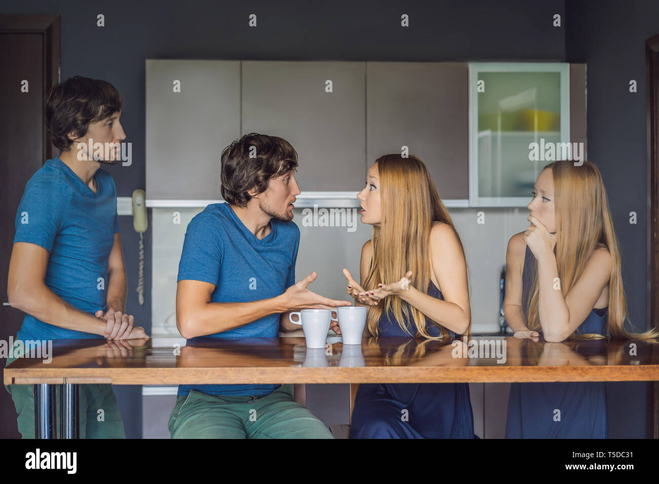 Young couple swears in the kitchen. Watch and evaluate their behavior from the side. Emotional intelligence concept - Stock Image