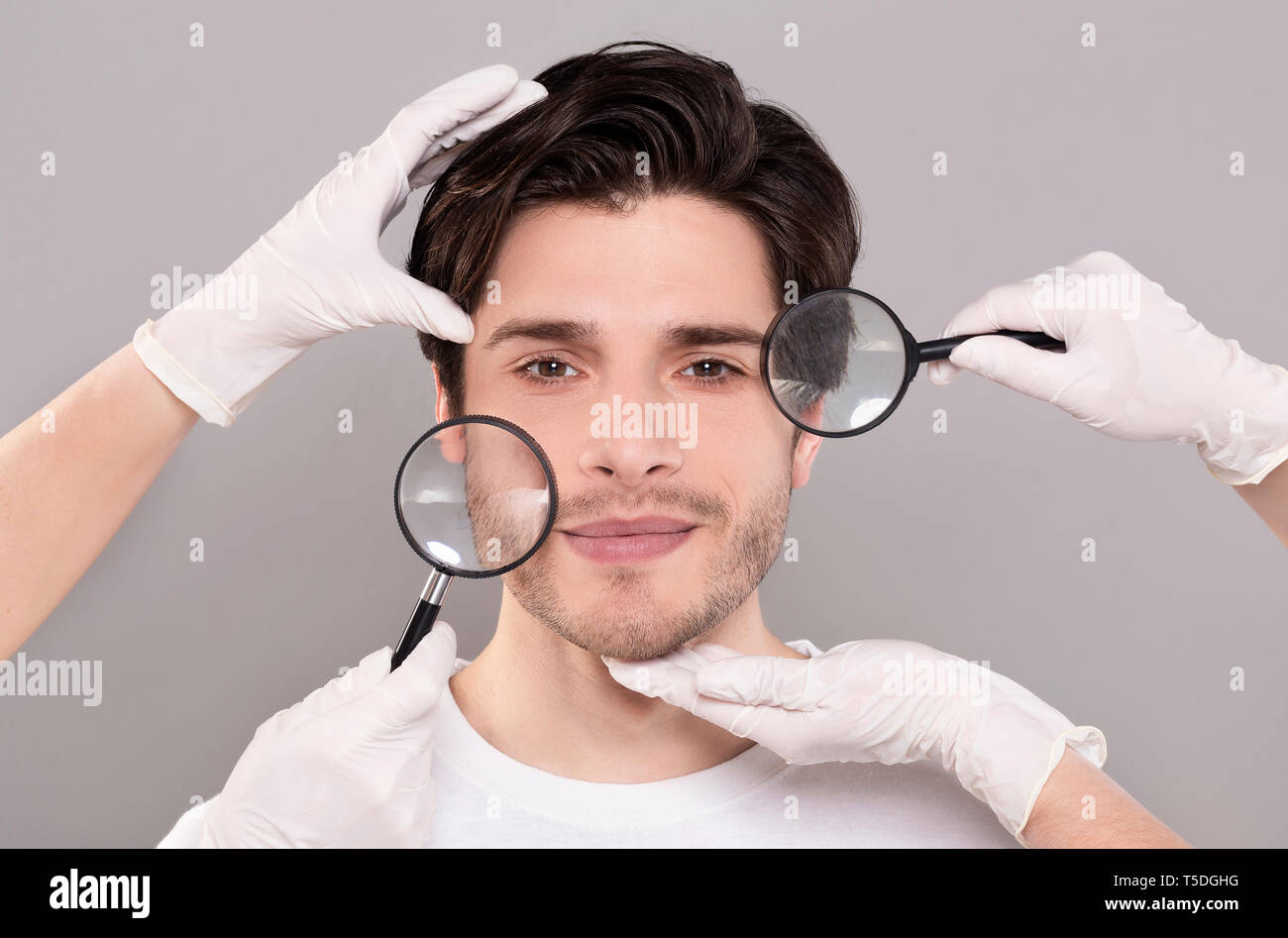 Face of young handsome man with beautician's hands and magnifiers - Stock Image