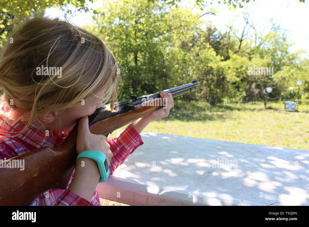 Girl with blond hair doing target practice with a 22 rifle - Stock Image