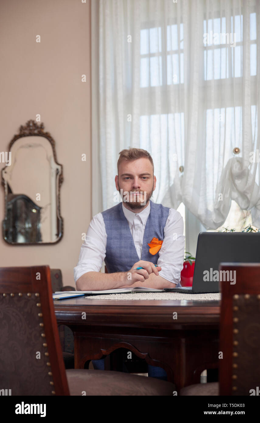 one young businessman, formal wear, posing for a portrait in his apartment room with antique furniture. - Stock Image