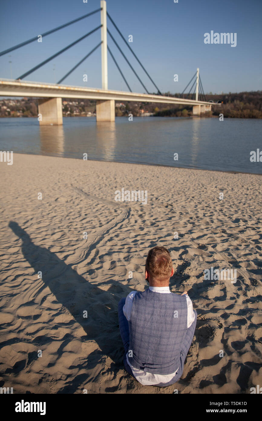 one young man, formal wear, sitting on beach alone, looking to river and bridge - Stock Image