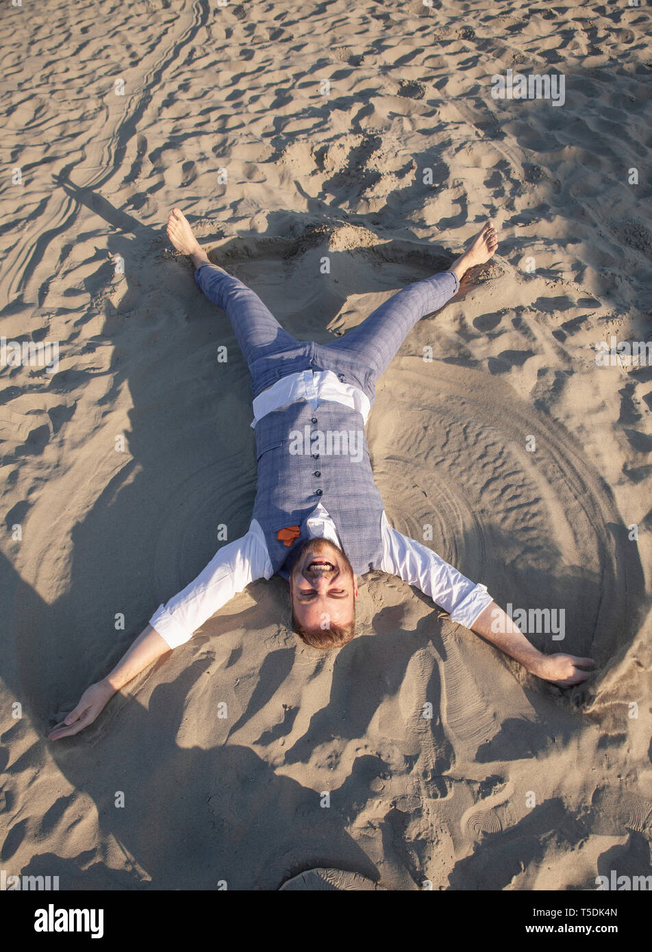 one young man, doing sand angel on beach. wearing formal wear, smiling to camera. - Stock Image