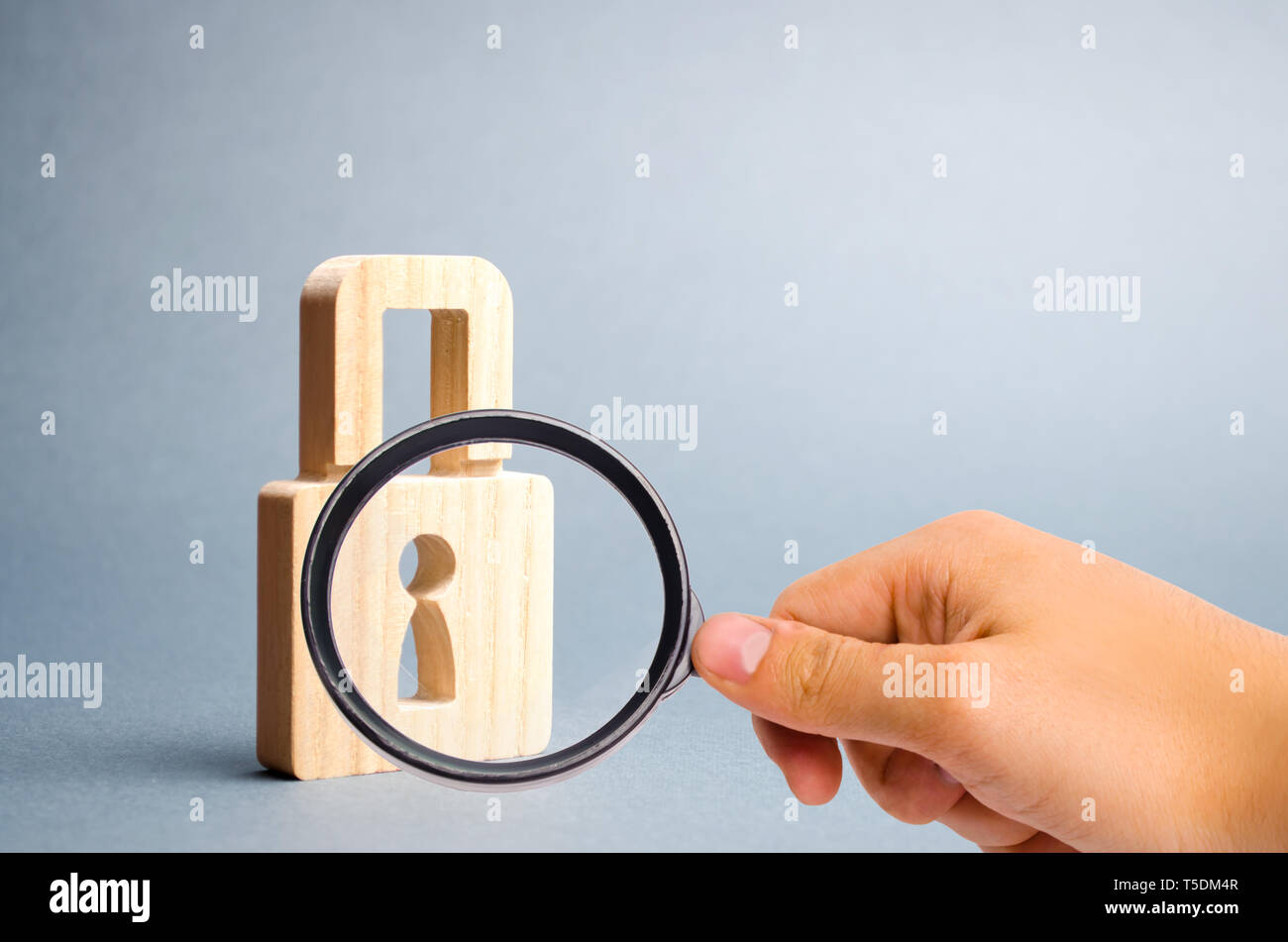 Magnifying glass is looking at the padlock on a gray background. information safty. concept of the preservation of secrets, information and values. Pr - Stock Image