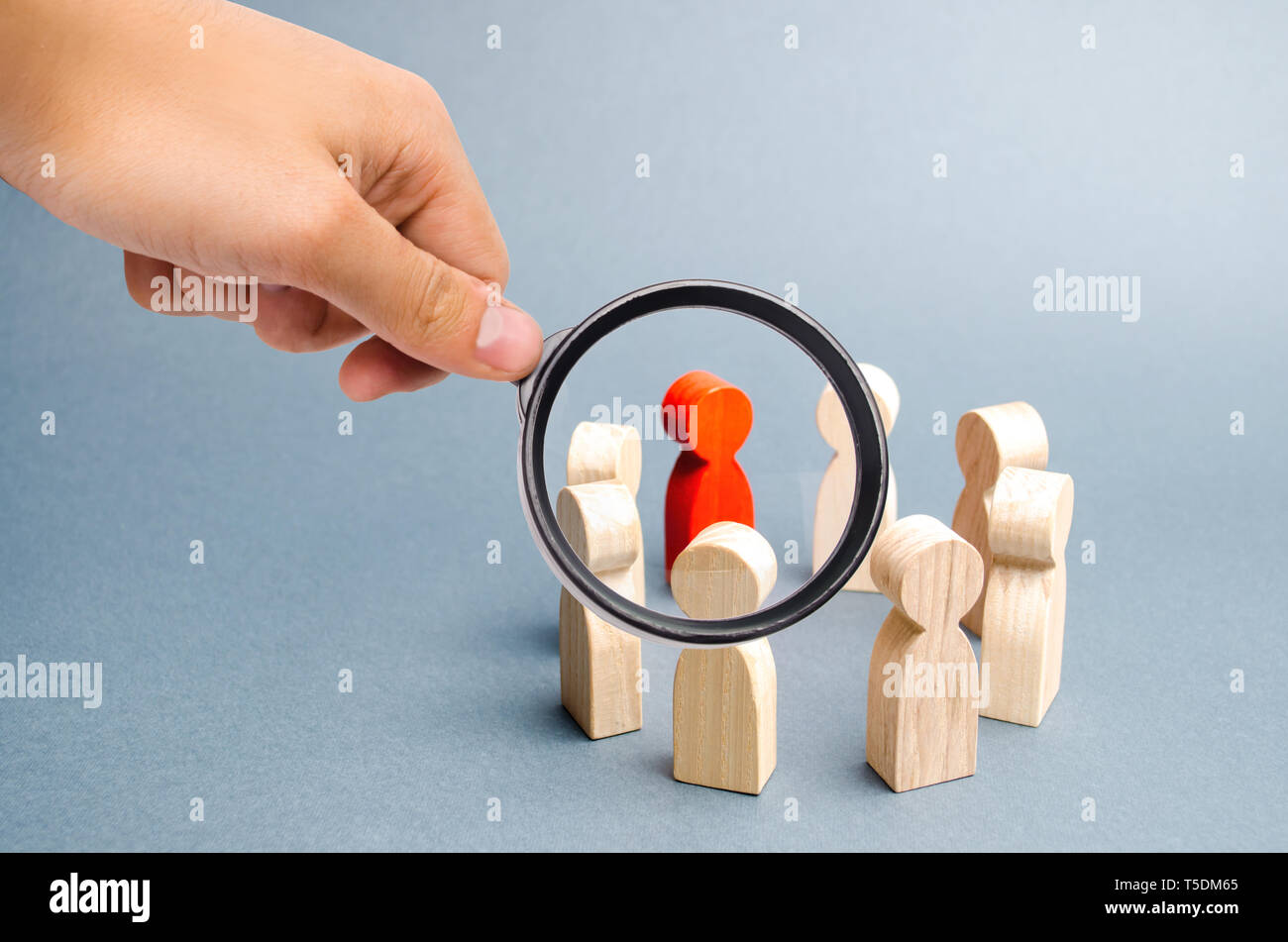 Magnifying glass is looking at the People stand in a circle on a gray background. Communication. Business team, teamwork, team spirit. Wooden figures  - Stock Image