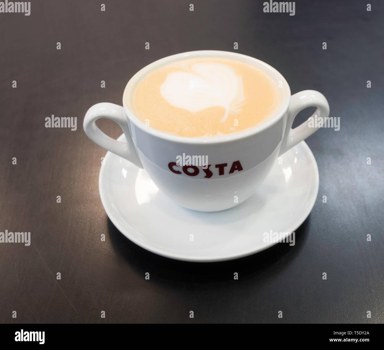 A large double handled cup of Costa latte coffee, England, UK - Stock Image