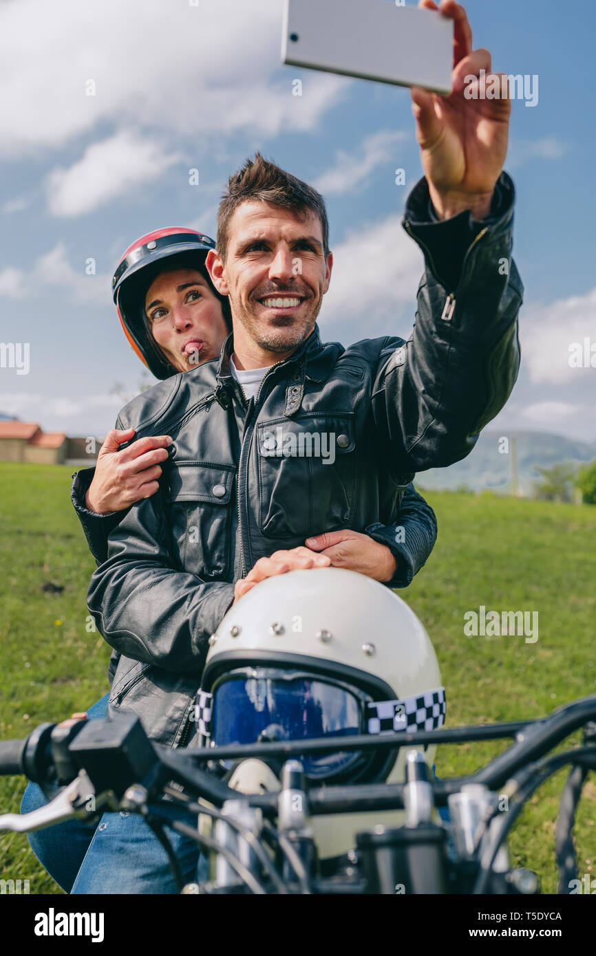 Young couple taking a selfie on the motorcycle outdoors Stock Photo