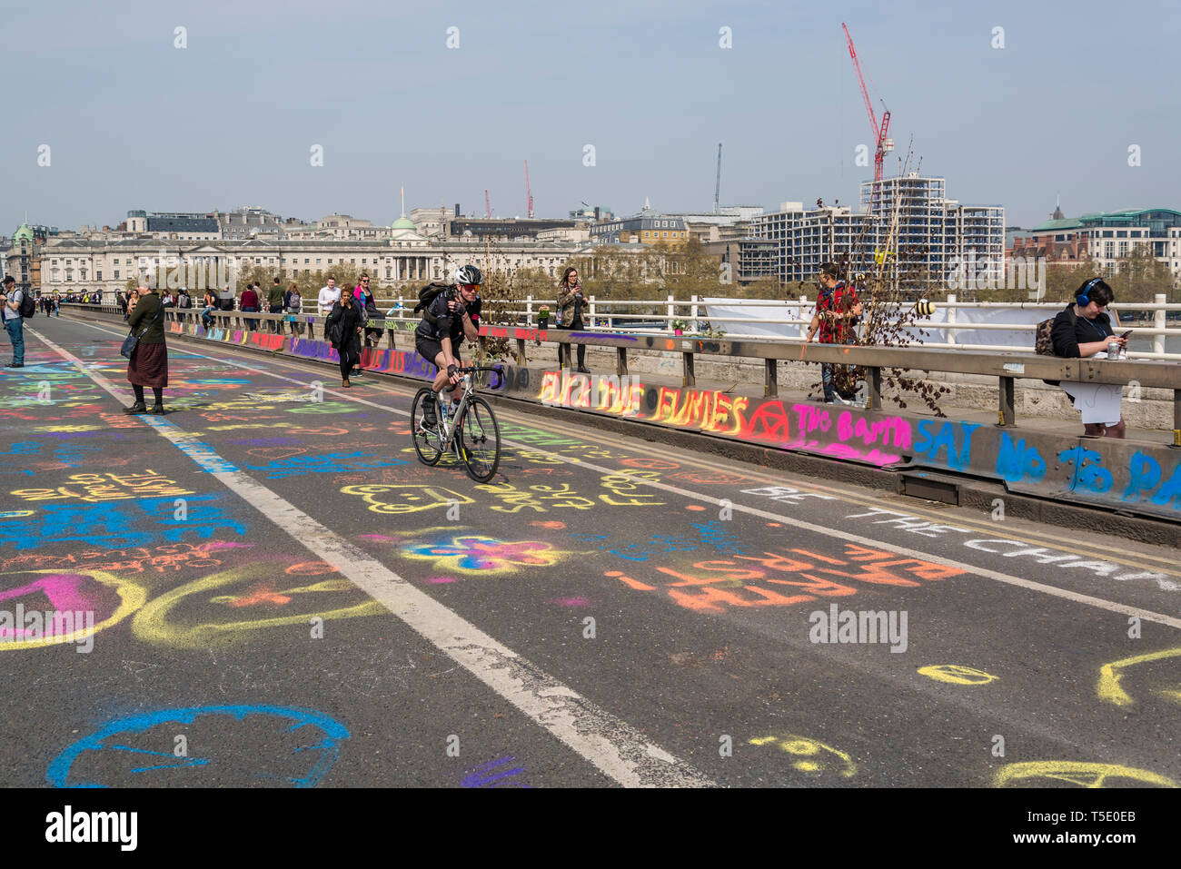 Extinction Rebellion protest on Waterloo Bridge, Road surface filled with colourfully written slogans and messages, London, UK - Stock Image