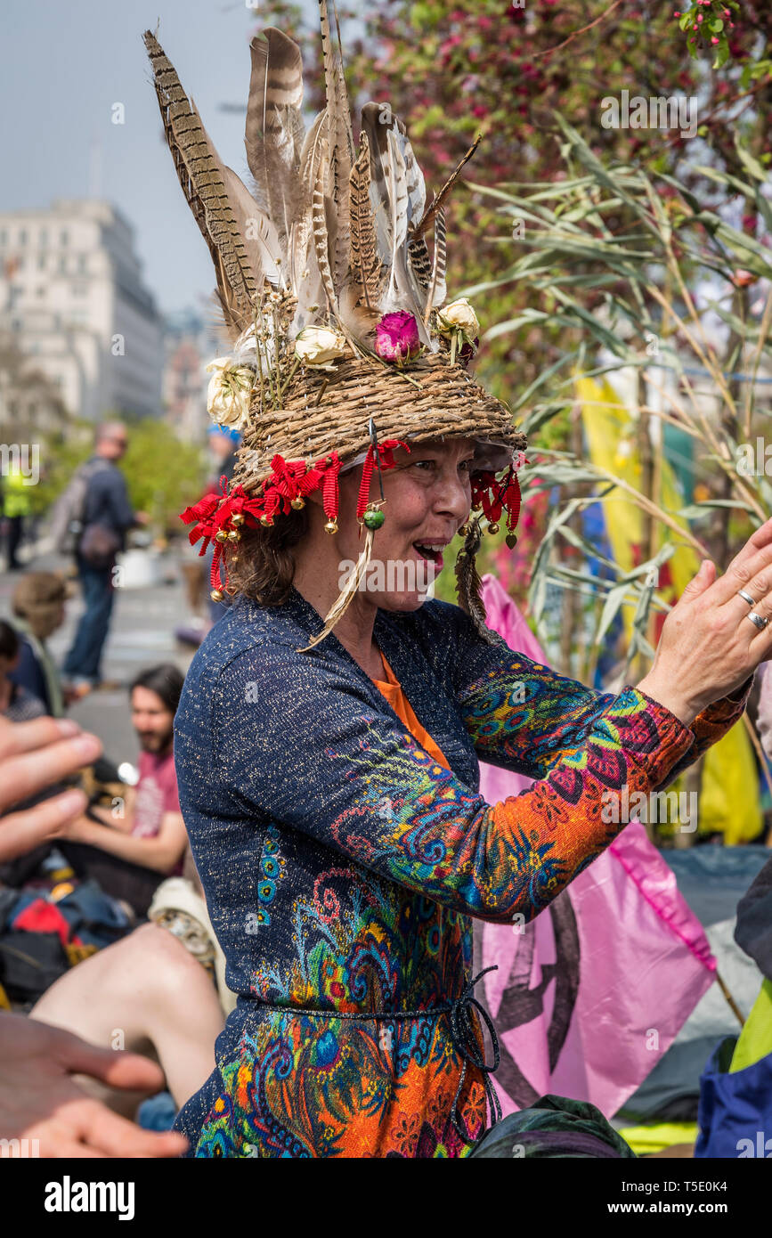 Extinction Rebellion protest on Waterloo Bridge, Colourfully dressed woman with lots of feathers in her hat clapping, London, UK - Stock Image