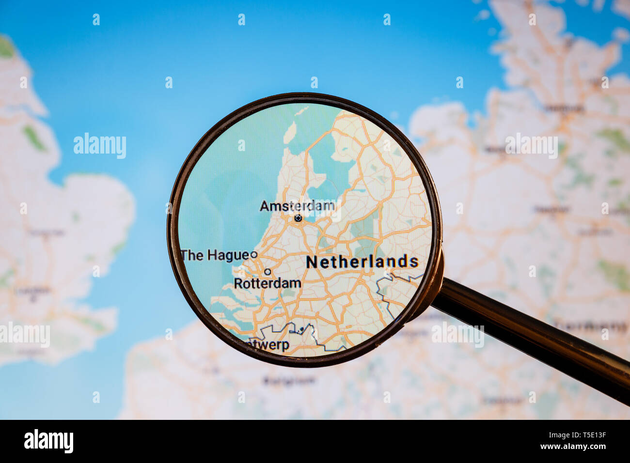Amsterdam, Netherlands. Political map. City visualization illustrative concept on display screen through magnifying glass. - Stock Image