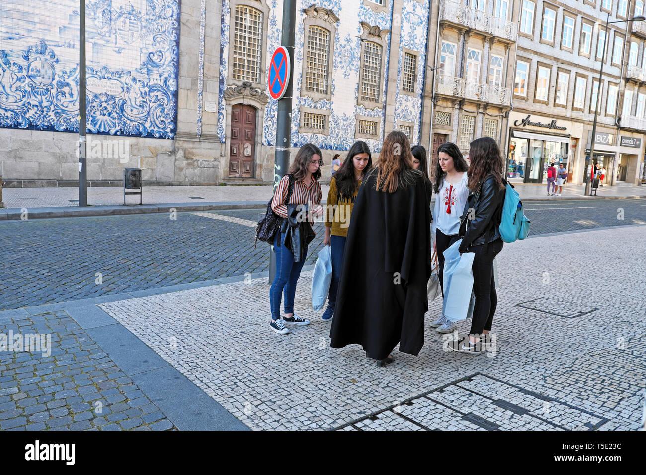 University female student in black cloak talking to friends in street Igreja do Carmo near Praça de Carlos Alberto Porto Portugal Europe KATHY DEWITT - Stock Image