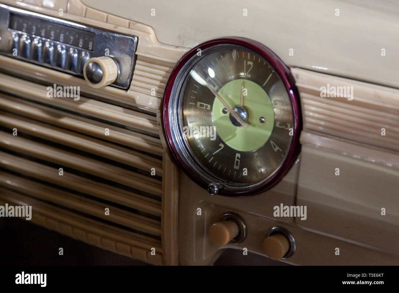 Vintage retro car dashboard with analog clock and audio radio system with buttons, handmade with wood and chrome for restoration - Stock Image