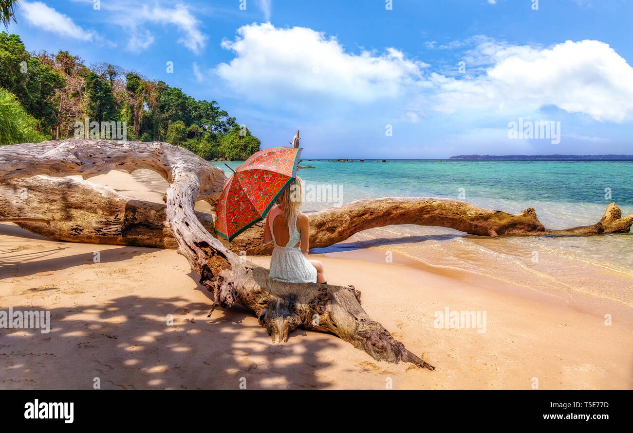 Young female tourist with umbrella sitting on a fallen tree trunk at the scenic Jolly Buoy island sea beach at Andaman islands India Stock Photo