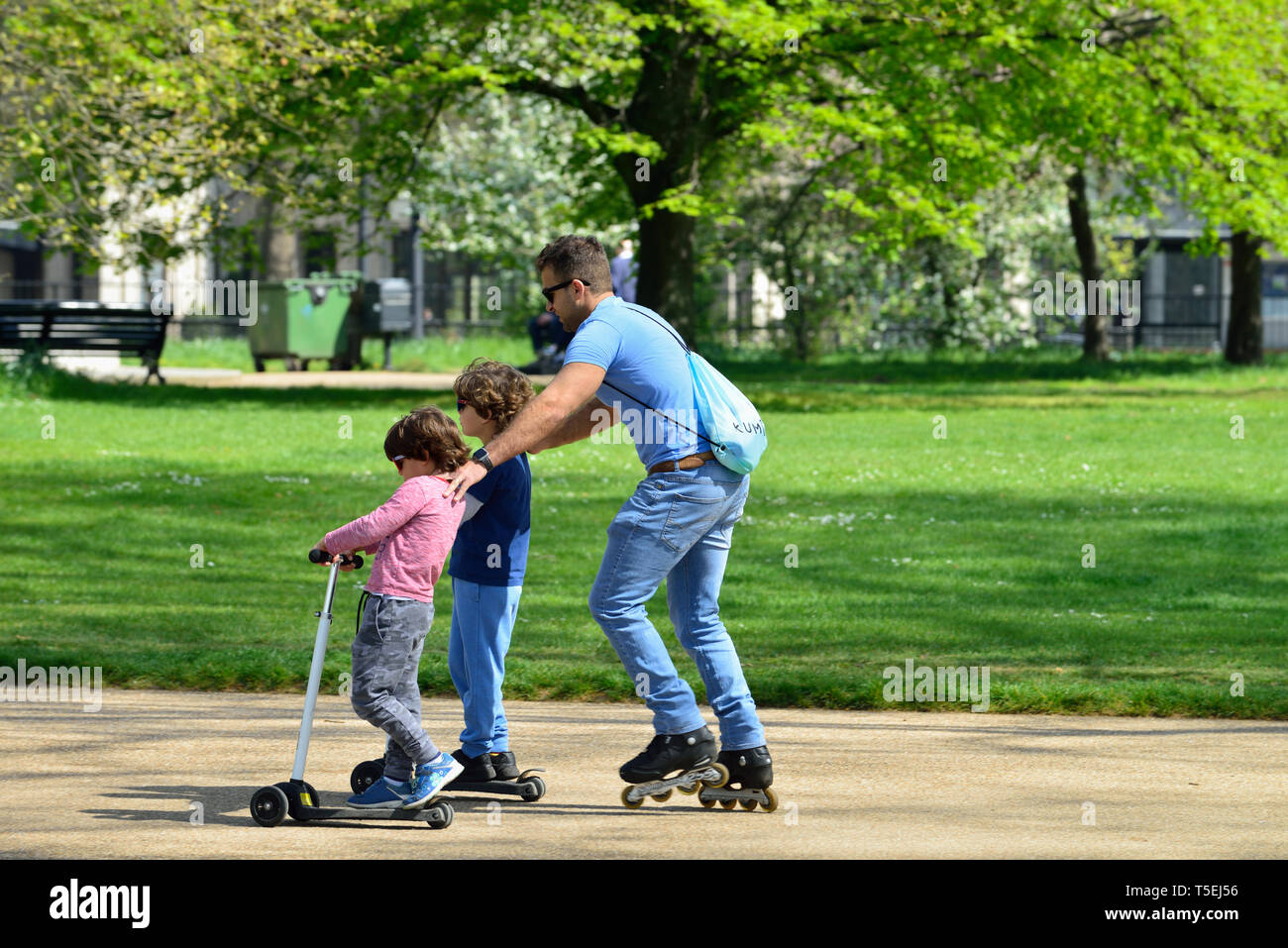 Father and sons on skates and scooters, Hyde Park, London, United Kingdom - Stock Image