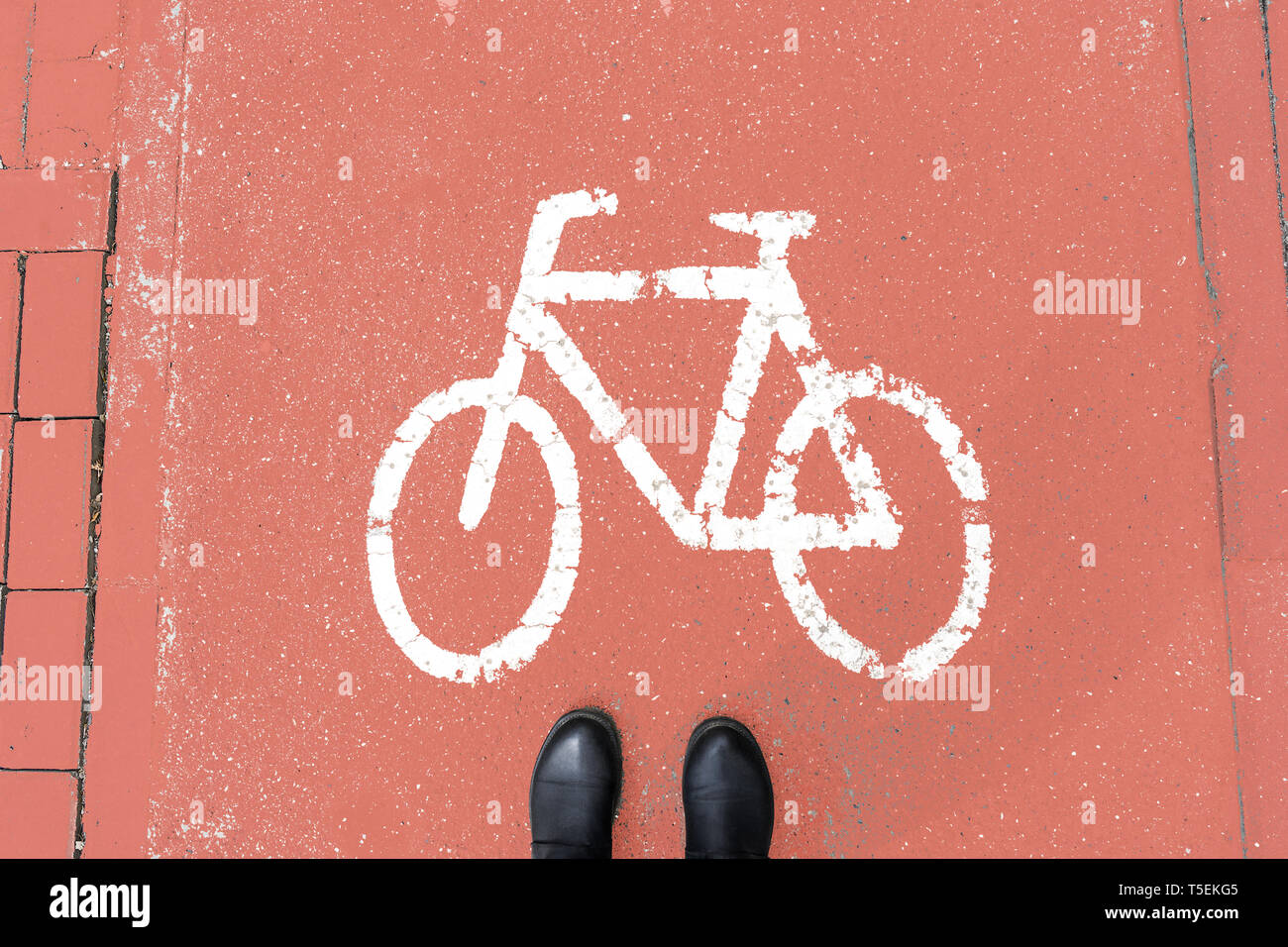 Pedestrian shoes on the coral-colored walkway for cyclists. Warning of danger. Stock Photo