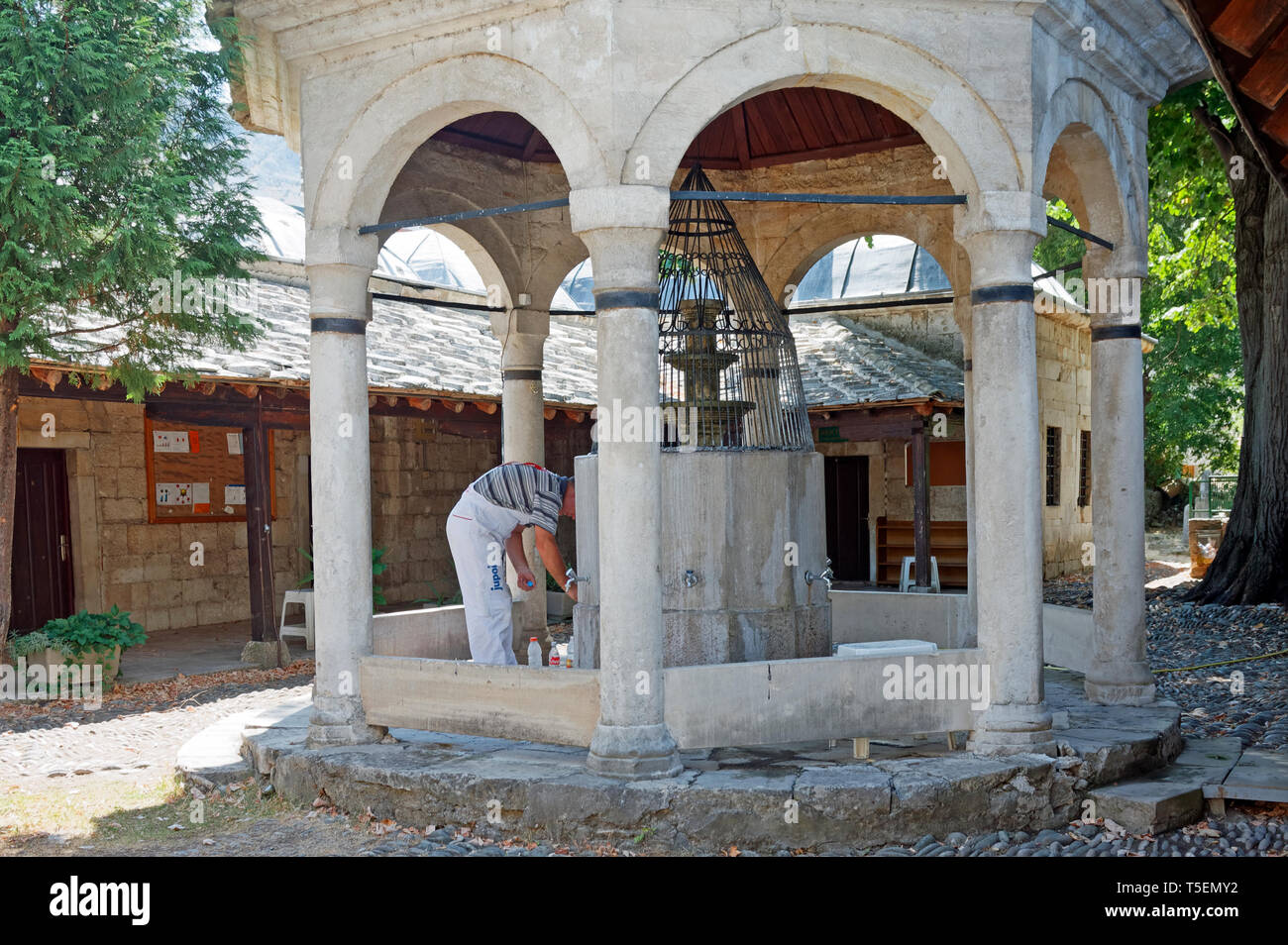 old stone ablutions fountain; mosque; workman filling bottles, religious building, Muslim, Mostar; Bosnia Herzegovina; Europe; summer, horizontal - Stock Image