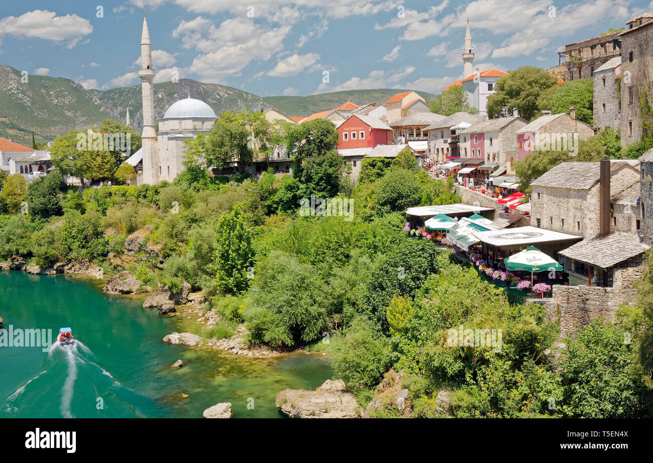 Neretva River overview; old buildings, outdoor restaurants, mosques, boat, water, scene, Mostar; Bosnia Herzegovina; Europe; summer, horizontal - Stock Image