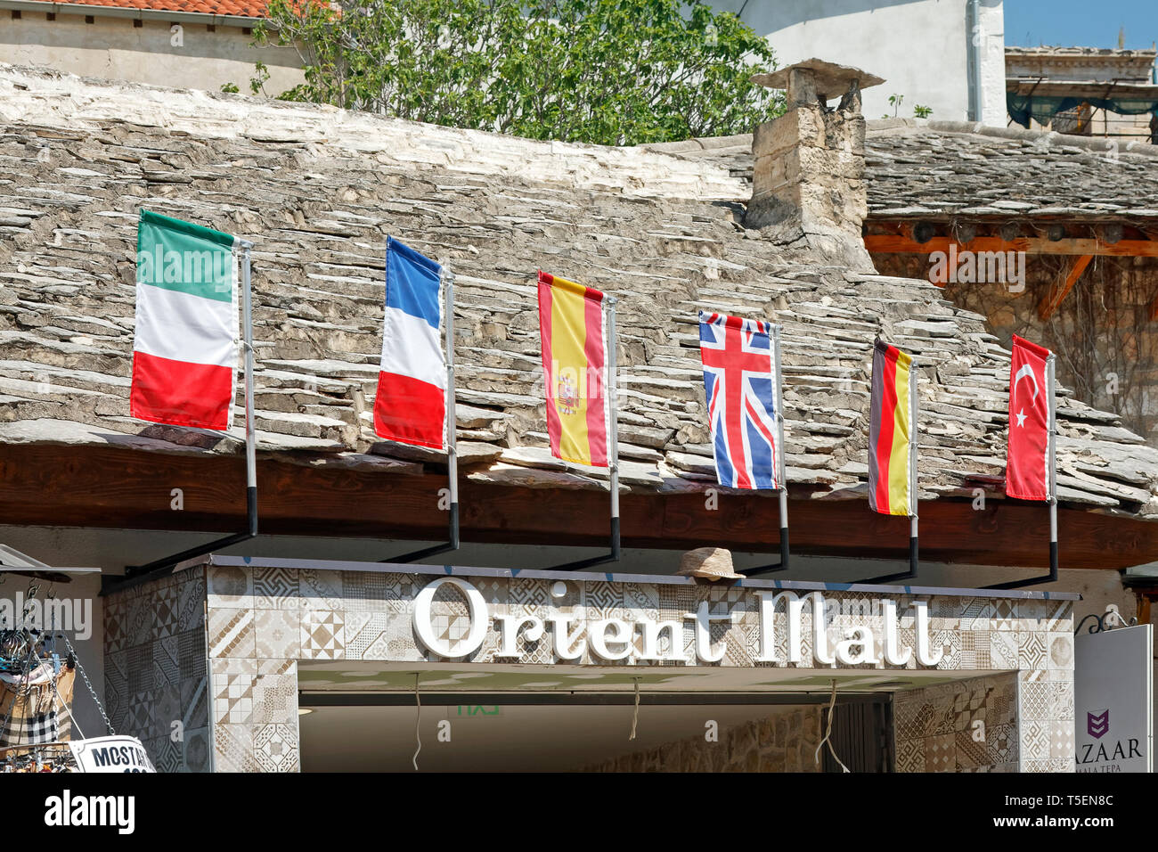 Orient Mall entrance, colorful country flags, old stone building, shops, Mostar; Bosnia Herzegovina; Europe; summer, horizontal - Stock Image
