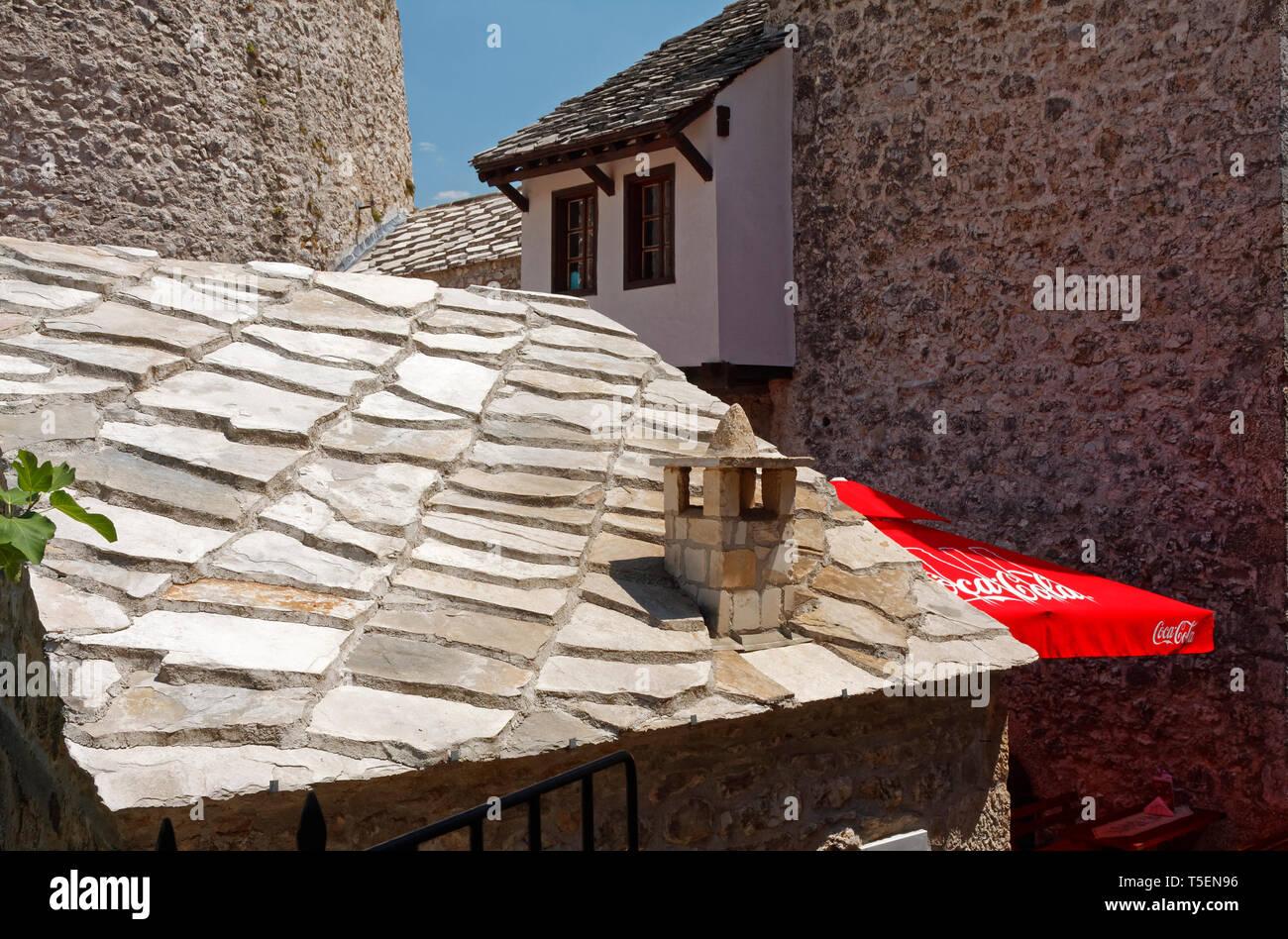 stone slab roof; heavy, old buildings; new red Coca Cola umbrella, contrast, Europe, Mostar; Bosnia Herzegovina;  summer, horizontal - Stock Image