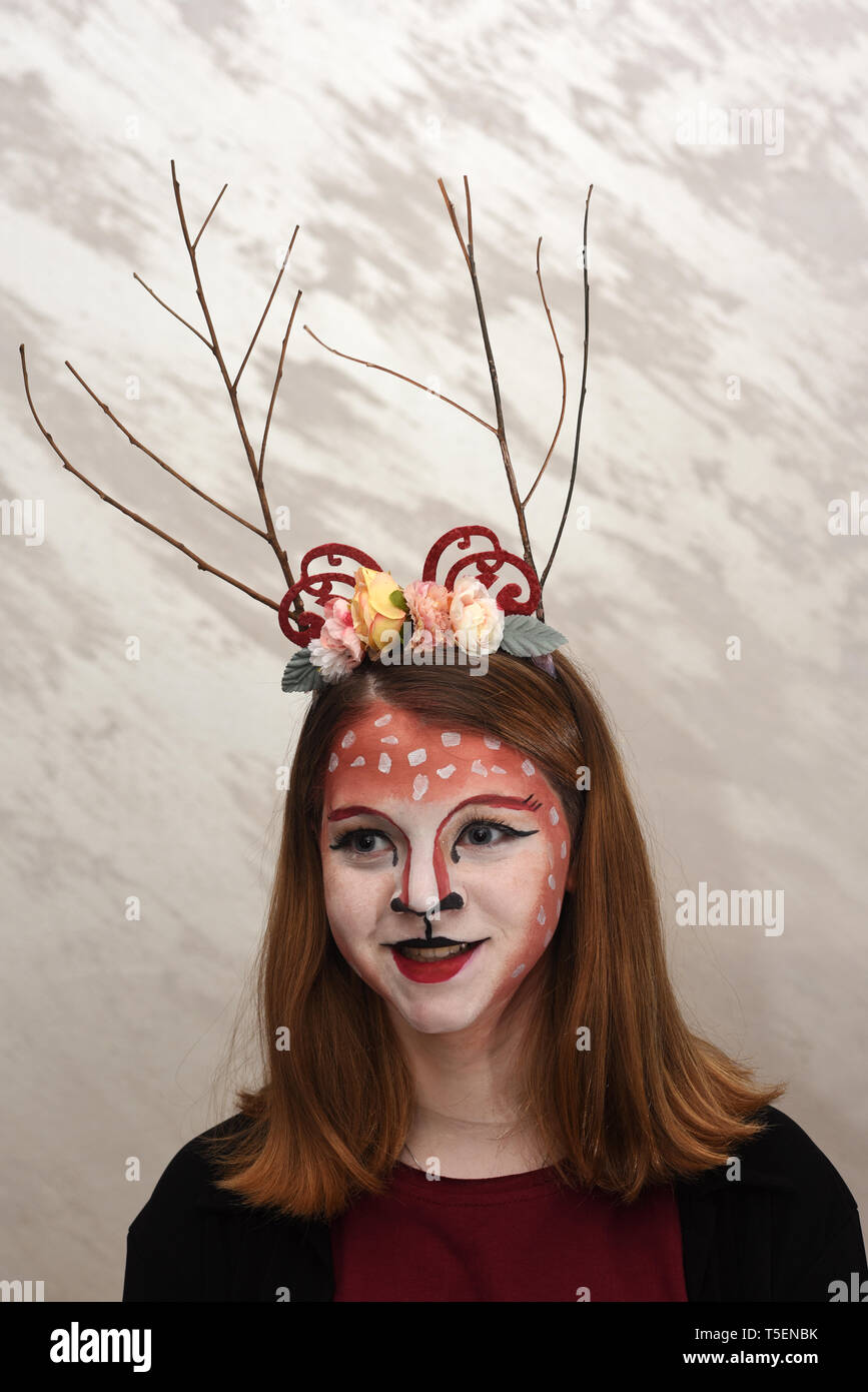 Young teen girl with body paint and costume dressed up as a forest fairy ready for a Halloween party - Stock Image