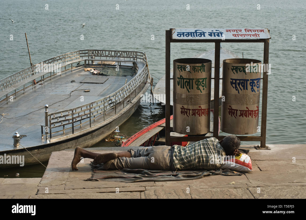 Poor man sleeping near public trash bins ( India). The scene takes place on a ghat, the Ganges river is visible in the background. - Stock Image