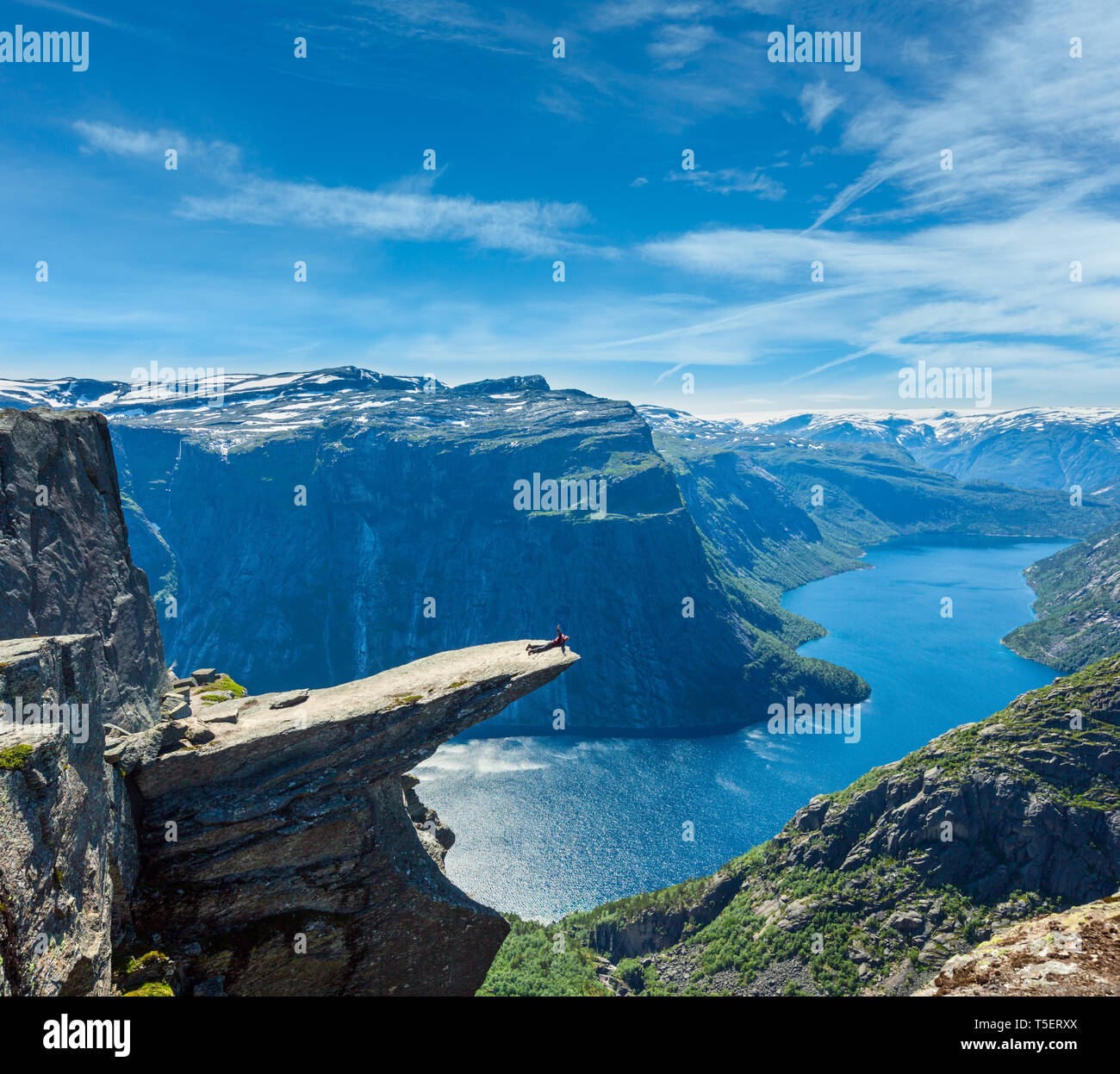 The summer view of Trolltunga (famous The Troll tongue Norvegian destination), Ringedalsvatnet lake in Odda, Roldal, Norway. And admire tourist on Tro - Stock Image