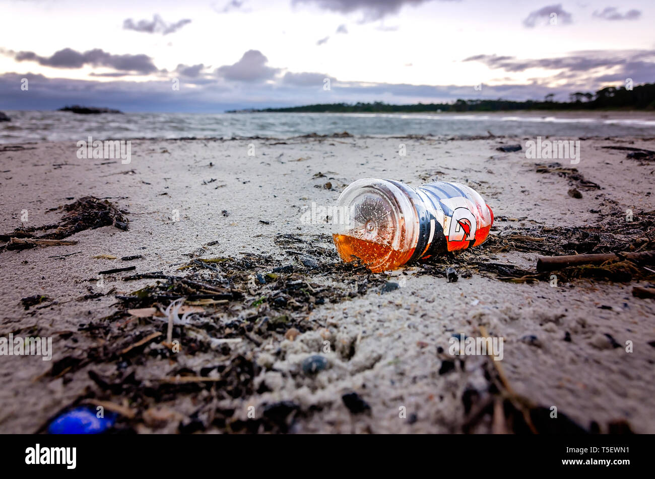 A plastic Gatorade bottle lays on the beach, April 19, 2019, in Dauphin Island, Alabama. - Stock Image