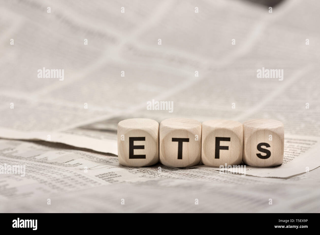 Exchange traded funds - wooden cubes on newspaper forming word ETFs Stock Photo