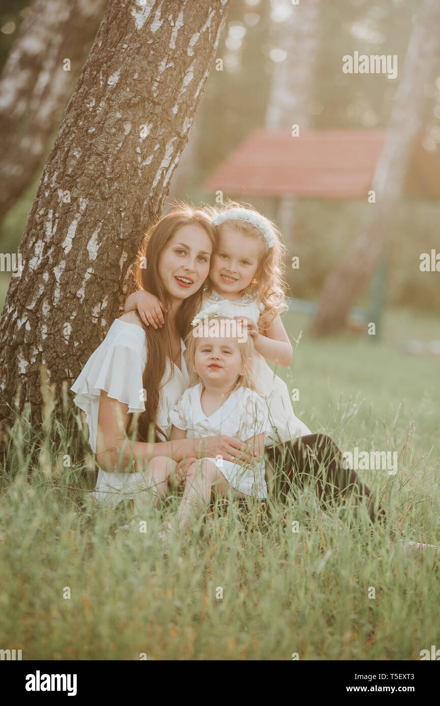Mother and two daughters whirling. Mother holds daughters on hands. Family time together. a wonderful portrait of mom with two daughters in the park - Stock Image