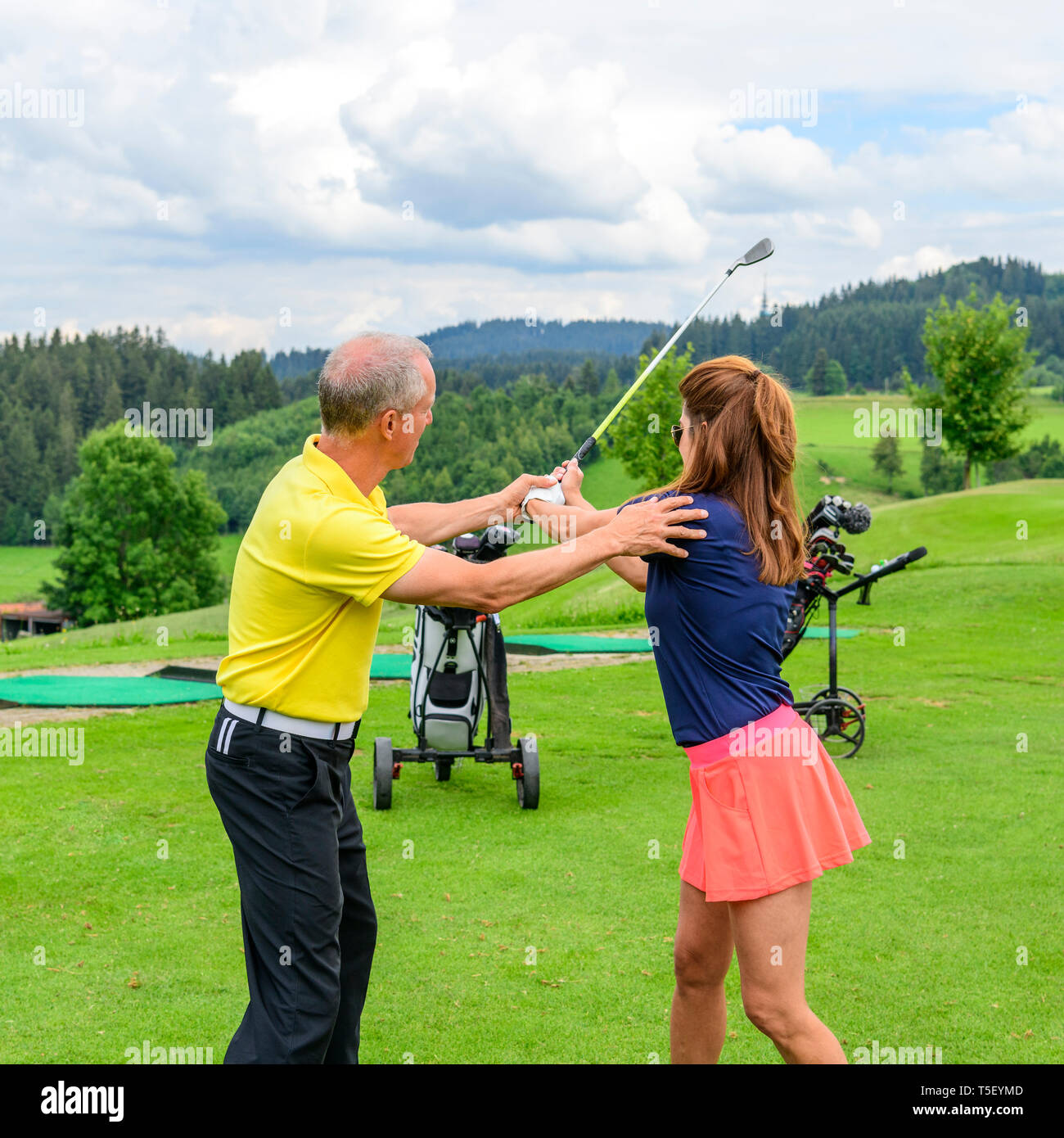 Golf players practising with golf pro on drivingrange - Stock Image