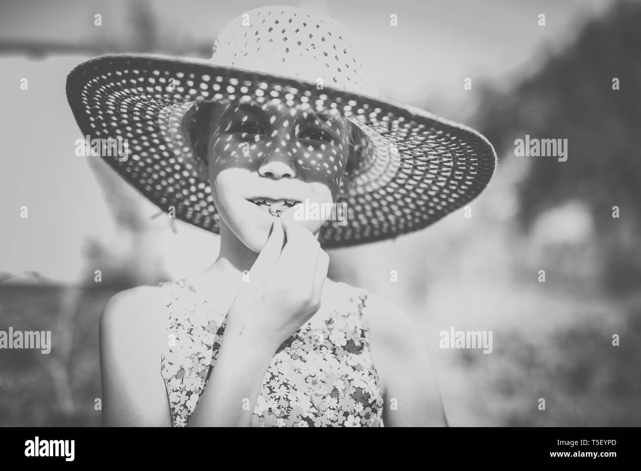 Adorable blonde girl in the big straw hat working in the garden. Teenage child helping in the farm. Stock Photo