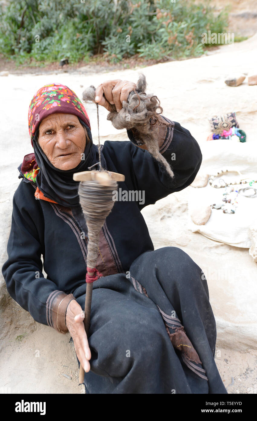 Old and weathered Bedouin woman spinning wool for weaving in Little Petra, Jordan. Stock Photo