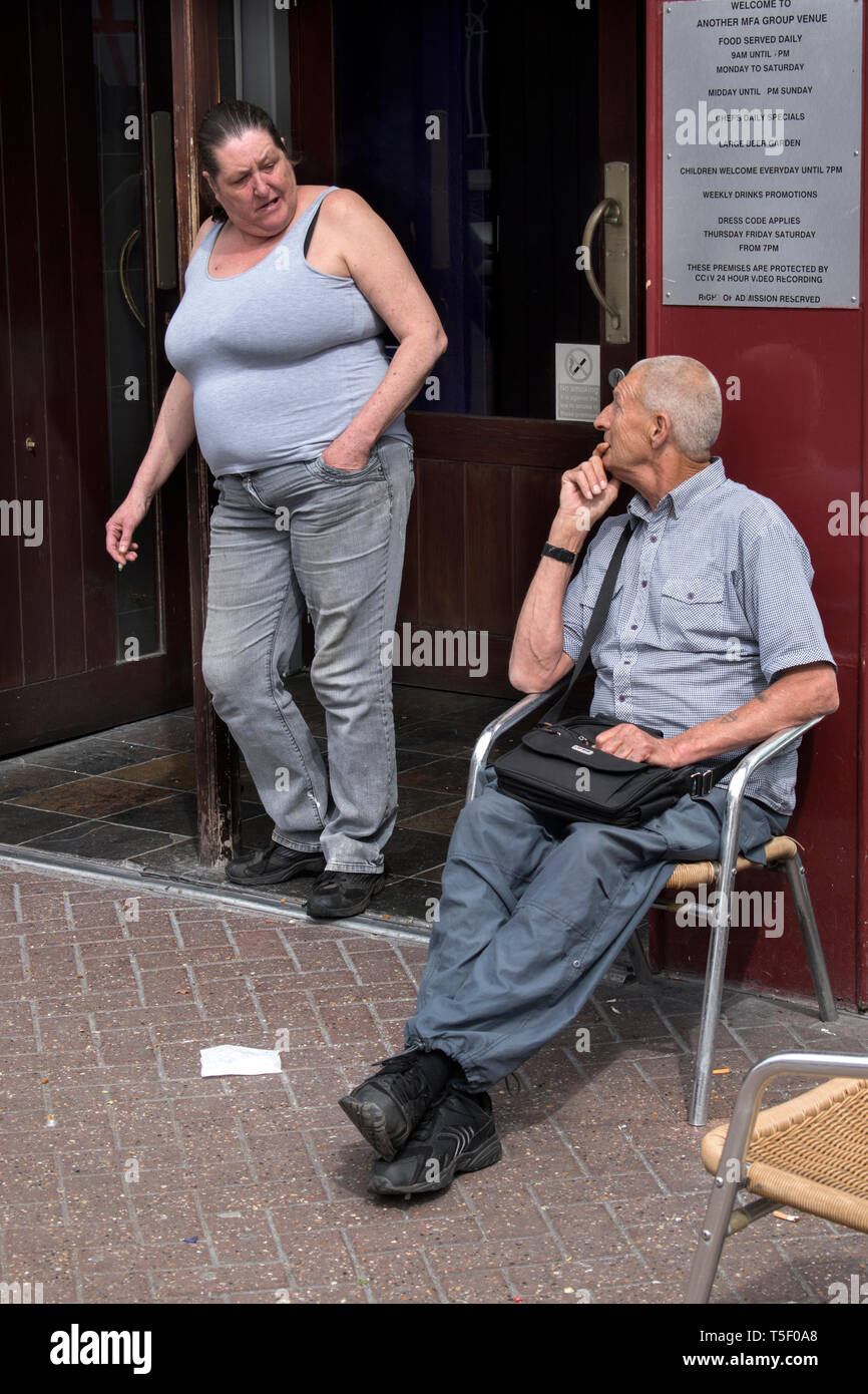 Working class white people man, woman, chatting outside an English pub, fat over weight out of condition, she is smoking. 2019 UK HOMER SYKES - Stock Image