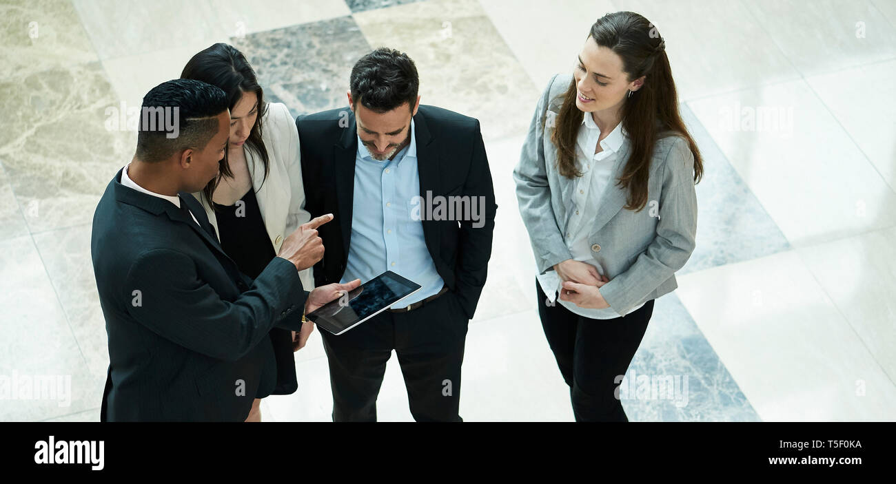 Business people discussing on digital tablet in hotel lobby - Stock Image