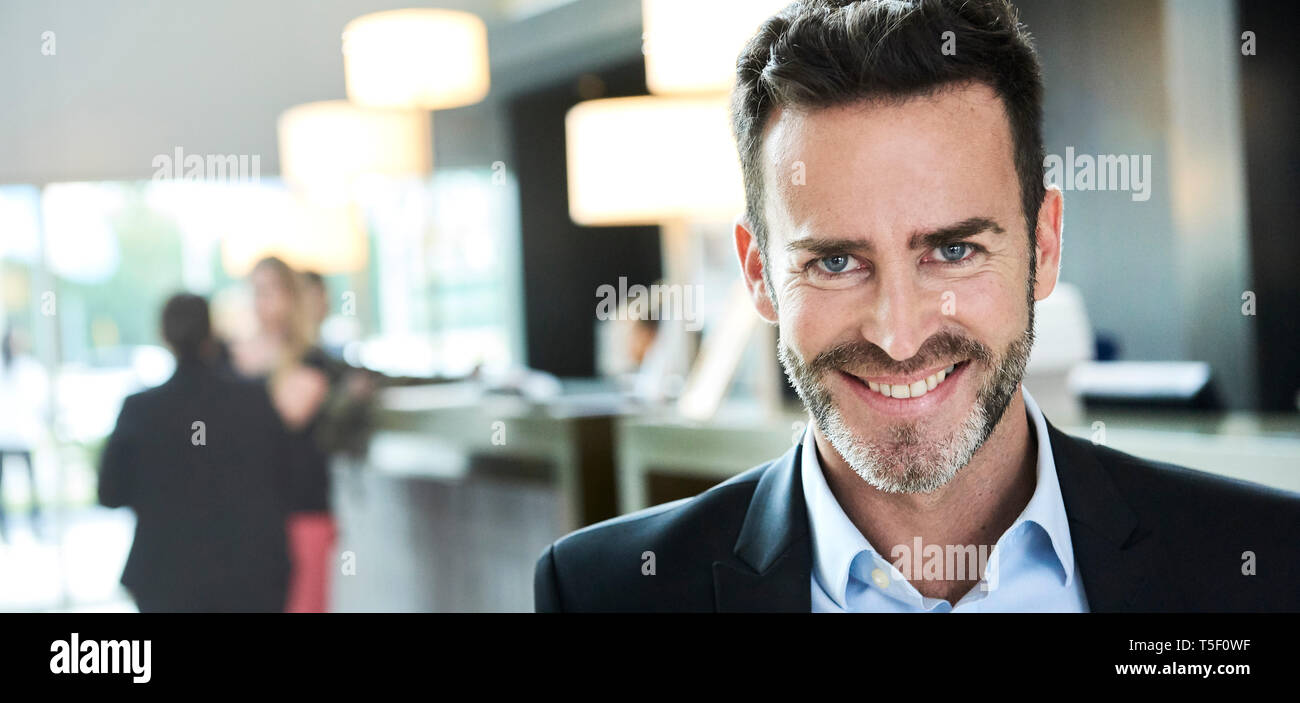 Portrait of businessman standing in hotel - Stock Image